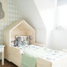 Prachtig houten kinderbed met aan het hoofdeind een huisje.