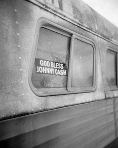 """God Bless Johnny Cash"" bumper sticker on a bus window. Road trip photo."