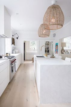 All-white kitchen with a marble island, and rattan pendant lights