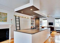 Cuisine contemporaine blanche avec plan de travail noir. Le faux plafond au-dessus de l'îlot central permet d'intégrer la hotte aspirante.