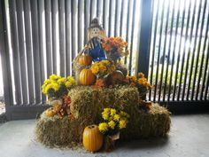 Outside fall decorations made with hay,scarecrow, pumpkins and fall flowers