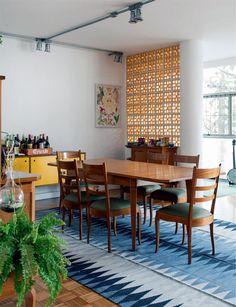 A mesa de jantar e as cadeiras, herdadas da avó da arquiteta, conquistaram lugar sobre o tapete da By Kamy. Ao fundo, aparador do Meu Móvel de Madeira. Os cobogós de cerâmica (Leroy Merlin) remontam aos anos 1960 e, ao mesmo tempo, atualizam o recorte na alvenaria.