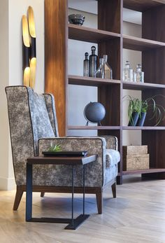 Isotta Armchair Black Tie Collection, piping, Central Station double shelf unit black walnut, Delightfull Coltrane Sconce, Chareau style end table Urban Archaeology, decorative accessories, custom bookcase