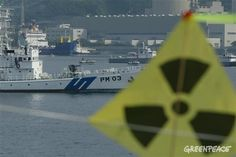 #The radioactivity sign in the foreground with military ship and MV 'Pacific Pintail' in the background in front of Takahama Nuclear Power Plant in Uchirua Bay, Japan. Surrounded by Japanese police and coastguard Greenpeace activists in inflatables are protesting in Uchiura Bay. The protest is addressed to BNFL ship 'Pacific Pintail' departing after being loaded with rejected weapons-usable Plutonium Mox fuel that is being shipped back to the UK. 07/04/2002 © Greenpeace / Jeremy…