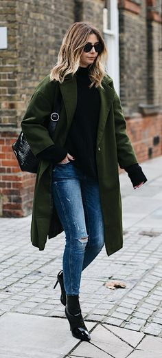 Emma Hill wears khaki coat, black sweater, ripped skinny jeans, black croc bag, round Rayban sunglasses, black pic vinyl patent angle boots, chic winter outfit