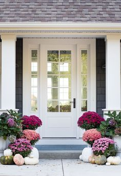 Purple fall front porch, dark grey sided home featuring mums in shades of purple with hints of faux orange florals and leaves
