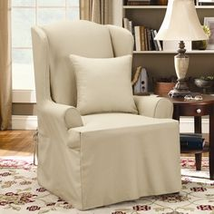 The Guides for Choosing Living Room Chair Slipcovers : Cozy Covered White Slipcover Chair Designed With Wing Back Plus Cushion Combine With Round Dark Brown Side Table And White Table Lamp Also White Rug With Brown Floral Motif On The Parquet Floor