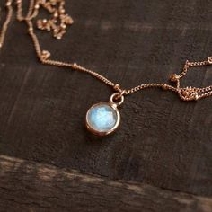 "Our Tiny Moonstone Necklace is a bohemian, yet simple necklace perfect for everyday wear. The coloring of the white, blue and purple stone paired with the exquisite rose gold filled satellite chain makes for an absolutely stunning and one-of-a-kind piece!FEATURES◊ Circular Rainbow Moonstone charm set in rose gold vermeil (rose gold layered over .925 sterling silver) ◊ Rose gold-filled satellite chain◊ Model is wearing 16"" length◊ All necklace findings are 100% rose gold-filled (chain, cl..."