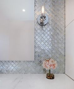 A frameless vanity mirror is hung from gray Moroccan trellis backsplash tiles lit by a glass and nickel sconce mounted over a washstand with a white quartz top.