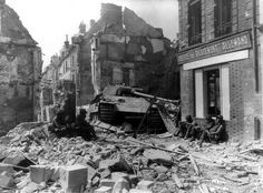 """GIs of 317th Infantry Regiment, 80th Infantry Division """"Blue Ridge"""" rest in the ruins of Argentan, rue de la Poterie, sitting at the foot of a Panther Ausf.G destroyed belongs to the II. / Panzer-Rgt. 33 of 9. Pz-Division. 21 August 1944."""