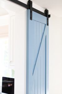 The barn door is painted in a soft blue color. barn door hardware. barn doors. barn door hardware. barn doors. barn door hardware. barn doors. barn door hardware. barn doors Patterson Custom Homes. Interiors by Trish Steele, Churchill Design.