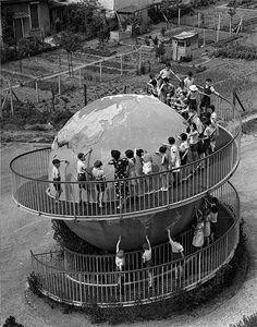 Pupils at a school in Paris learning their geography from a giant globe in the playground, 1938