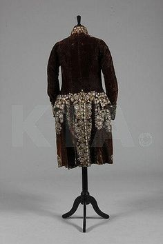 BAck view, 3-piece court suit, France, 1790. Dark brown velvet with magnificently embroidered and irridescent paste studded flowerheads and foliage; waistcoat: ivory silk satin with similar embroidery.