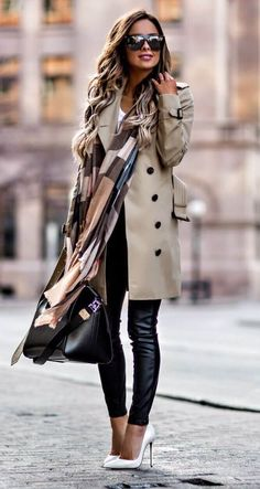 Beige trench coat with black jeans and print scarf.
