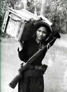 Female member of Vietnamese Popular Forces (South Vietnamese village defense) unit carries ammunition box. circa 1967.