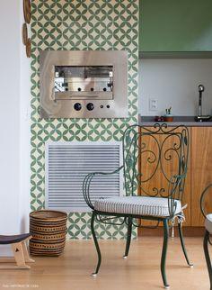 varanda integrada com a sala com churrasqueira revestida de ladrilhos hidráulicos verdes e cadeiras de ferro