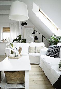 Aranżacja białego salonu na poddaszu w stylu skandynawskim. Jasną przestrzeń dodatkowo rozświetlają okna dachowe....