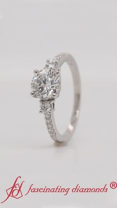 This petite three stone diamond ring a features a brilliant round cut diamond held in the center with two round cut diamonds in a basket prong setting of either side of the center stone along with small shimmering round diamonds arranged in micro pave setting of the ring shank to add an aesthetic touch to your look. #fascinatingdiamonds #labdiamondring #ring #platinumring #engagementring #labdiamondengagementring #womensring Three Stone Diamond Ring, Three Stone Rings, Round Cut Diamond, Lab Diamonds, Round Diamonds, 3 Stone Engagement Rings, Best Diamond, Platinum Ring, Shank