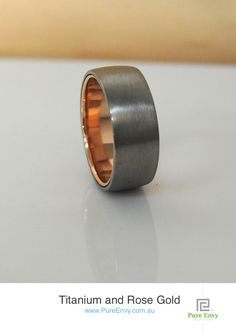 Men's 2 Tone Ring - Titanium and Rose Gold Wedding Band. Custom made with strong and robust outside Titanium Skin, with Rose Gold inner sleeve. Available in colour combinations of Rose, Yellow or White Gold inner sleeves. Features a textured Titanium skin with durable and grey tones and comes in 6 & 8mm wide from $(see website)