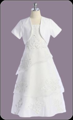 Three fluttering organza tiers cascade down a spaghetti strap white Communion dress that is adorned with elegant floral embroidered appliques, shimmery sequins and a matching satin bolero jacket.