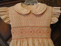 """Any smocked to the shoulder pattern will work.  I used """"Anne"""" from Australian Smocking & Embroidery #78 adapted with an angel sleeve and ruffled collar.  Plate is an original design.  Peach floral from Fabric Finders."""