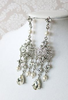 This pair of bridal earrings are the glamorous Victorian style sparkling chandelier earrings featuring a spray of sparkling crystals and Swarovski pearl of various sizes. For dazzling style, keep focus on these show stopping earrings by keeping all other jewelry to a minimum. Or, for dramatic style, coordinate with a bejewelled cuff bracelet and sparkling headpiece.    Beautiful wedding earrings for brides who adore classic vintage style, these beautiful bridal earrings make a statement and…