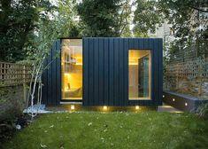 bureau de jardin moderne avec fenêtres panoramiques, bardage bois gris anthracite et parement extérieur en pierre