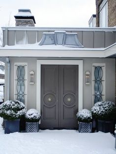 A blanket of winter white snow covers the front garden of this live work space in the Netherlands. Double carved front doors painted a cool glossy grey, manicured hedges in symmetrical planters and wonderful iron work over the door's sidelights make for a grand entrance. (above)