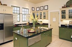 These homeowners made clever paint choices. By selecting a dark green for the base cabinetry and island, they grounded the space with an appropriate connection to nature. Pale gold upper cabinets bring a welcomed lightness to the scheme. Interestingly, the units with glass-panel doors reveal that the same shade of green is used within.