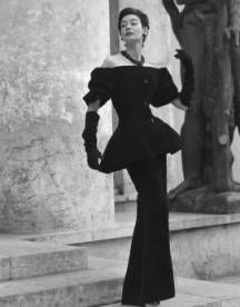 Christian Dior dinner ensemble in black nylon and rayon velvet, August 1954 collection.  Black nylon and rayon velvet, shows the restrained, yet flattering bosom lines that are typical of his current Paris collection. Dress has long slim lines, while short, shoulder baring coat is flat over the bosom, full and flaring below the waistline. The fabric, Velvenyl by Raimon, was acclaimed a sensation in Paris. Because it contains nylon, it resists crushing and marring.