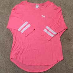 VS pink jersey shirt large Victoria's Secret Pink Nation shirt *limited edition and only avaliable to members at the time. No longer available.* Lighter neon pink color with white striped sleeves and PINK NATION on back.  Brand new no signs of wear or anything  Worn once around my house (wasn't for me) Size lg, true to size PINK Victoria's Secret Tops Tees - Short Sleeve