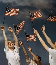 ca. July 1942, New York City, New York, USA --- Girls wave American flags in the air to encourage people to buy war bonds.