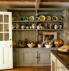 Bunny Williams ~ A 19th century French dresser found in a bakery in the Dordogne displays a collection of earthenware and majolica against one wall of this rustic kitchen