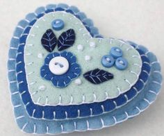 Felt hanging heart with layers of applique and embroidery in blues and white, embellished with tiny buttons. A perfect Christmas gift or decoration . 9cm x 8cm approx, with a ribbon loop for hanging.