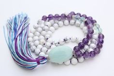 Mystic Light Mala is hand knotted with 8mm Amethyst, Green Fluorite, and White Howlite on natural silk cord and finished with a sleek silk tassel. 108 beads + Guru Amazonite. .925 Sterling Silver accents. _____________________________  Amazonite Amazonite, a luscious shade of turquoise harnesses the powers of Truth and Courage. Worn by ancient Amazonian warriors, this stone is thought to empower the user by allowing her to speak her mind freely and without inhibition. It connects with the…