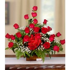 Arreglo floral con 24 botones de rosas rojas y un toque de baby's breath, en nuestra clásica caja de madera finamente decorada con cinta de mantequilla.