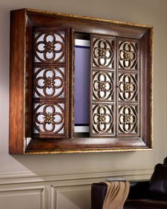 """Sort of the idea I had.    """"Quatrefoil"""" Plasma TV Entertainment Cabinet by John-Richard Collection at Horchow. The bi-fold doors of this wall-mounted entertainment cabinet with gothic quatrefoil front panels can cleverly conceal a flat-screen TV behind their antiqued mirrored glass. Sable finish has broken gold leafing and the quatrefoil design panels have cavetto molded frames."""