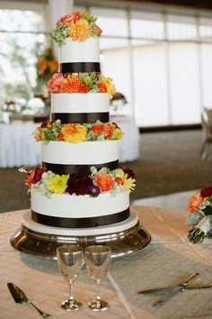 The cake itself was a four tiered buttercream cake with flowers in between each layer. The color scheme of the wedding was kept intact by using green cymbidium orchids, yellow, orange, and red dahilas, antique green hydrangea, cherry brandy roses, mango calla lilies, and purple aster | by Dorothy McDaniel's Flower Market; Spindle Photography