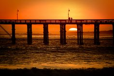 Rich orange glow of a setting sun over the pacific ocean as seen through the pier in Ventura, California. From aldendale.com