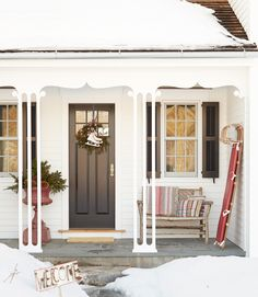 A sled, tiny welcome sign, and skis adorn this winter wonderland porch of this cozy Connecticut farmhouse.
