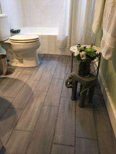 Painted linoleum flooring made to look like weathered wood tile.