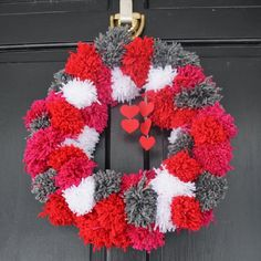 Tie red, white, and pink yarn pom poms around a wire hanger, shaped into a circle, to create a lovely wreath for Valentine's Day.