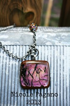 Brown fused glass is adorned with a beautiful piece of pink shimmer glass. Black stringer perfects this piece to go perfectly with any outfit. Pink shimmer focal bead, with rhinestone accents top it all off. Chain antiqued silver rollo chain 19 inches long. Swivel clasp allows you to latch onto a...
