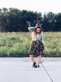 Awesome LuLaRoe Outfit, LuLaRoe Lynnae long sleeved Top, LuLaRoe Madison pleated Skirt with pockets, Stella and Dot tassel necklace, top knot bun, and Free People Mont Blanc Sandal in black.