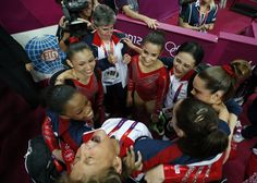 Marta Karolyi, foreground, U.S. national women's gymnastics team coordinator, arches her back as she laughs and celebrates with team U.S. after they won the gold medal at the Artistic Gymnastics women's team final at the 2012 Summer Olympics, Tuesday, July 31, 2012, in London.