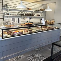 Tserki Pastry Shop - Interior, industrial design, pendant lighting, wooden furniture for product display, metal display window, floor tiles black & white pattern, greek island, paros