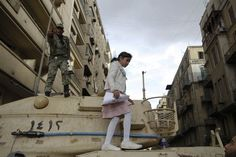 An Egyptian soldier gestures as a child walks on top of an army tank in Tahrir Square in Cairo.