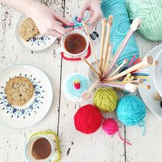 Yarn balls on table with crochet hooks & knitting needles in a jar in the middle!