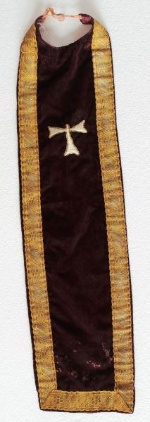 El traje de la imagen de San Antón se completa con este peto en el que campea la Cruz de San Antón, cuya forma responde a la letra tau del alfabeto griego.
