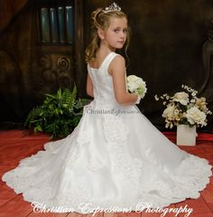 This long length satin first communion gown features heavy beading throughout with exquisite pearl details along the neckline and arms. The skirt offers a split design with additional beading and lace details and lace hem.